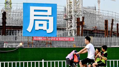 A man and children cycle past the Guangzhou FC football stadium, which is being built by Evergrande.