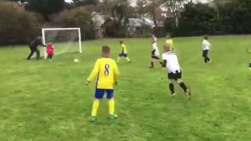 A dad about to push his goalkeeper son to stop the ball going into the net
