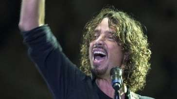 Chris Cornell on stage, raising his hand high as he plays guitar