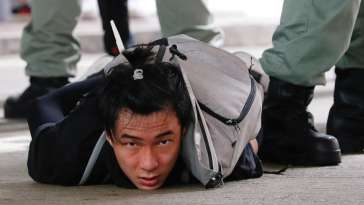 A man lies on the ground as he is detained by riot police during a march against the national security law